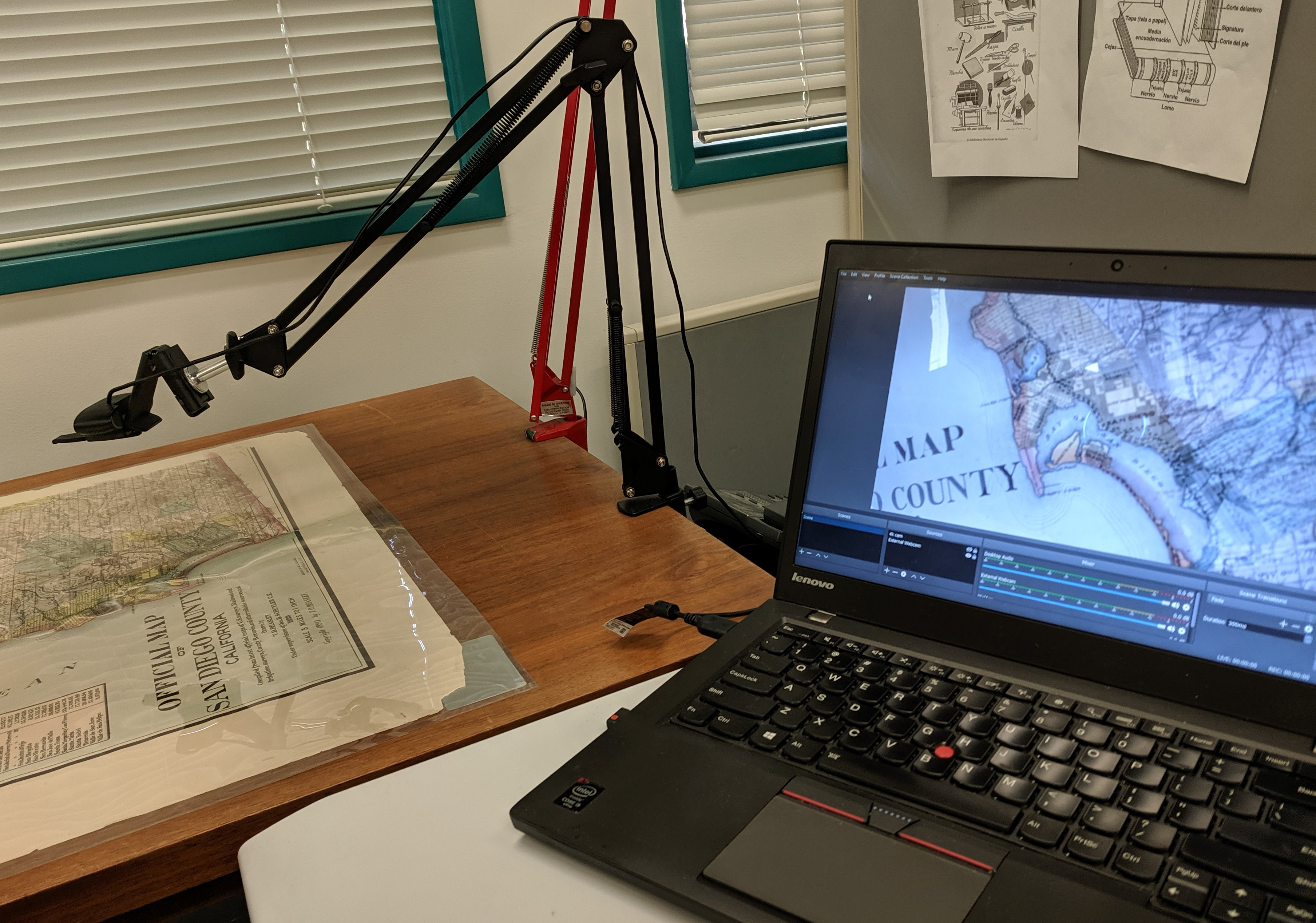 A HoverCam attached to a moveable arm, on the left side of the photo,, captures an image of a large map of San Diego County. The image captured by the HoverCam is seen on the screen of a laptop on the right.