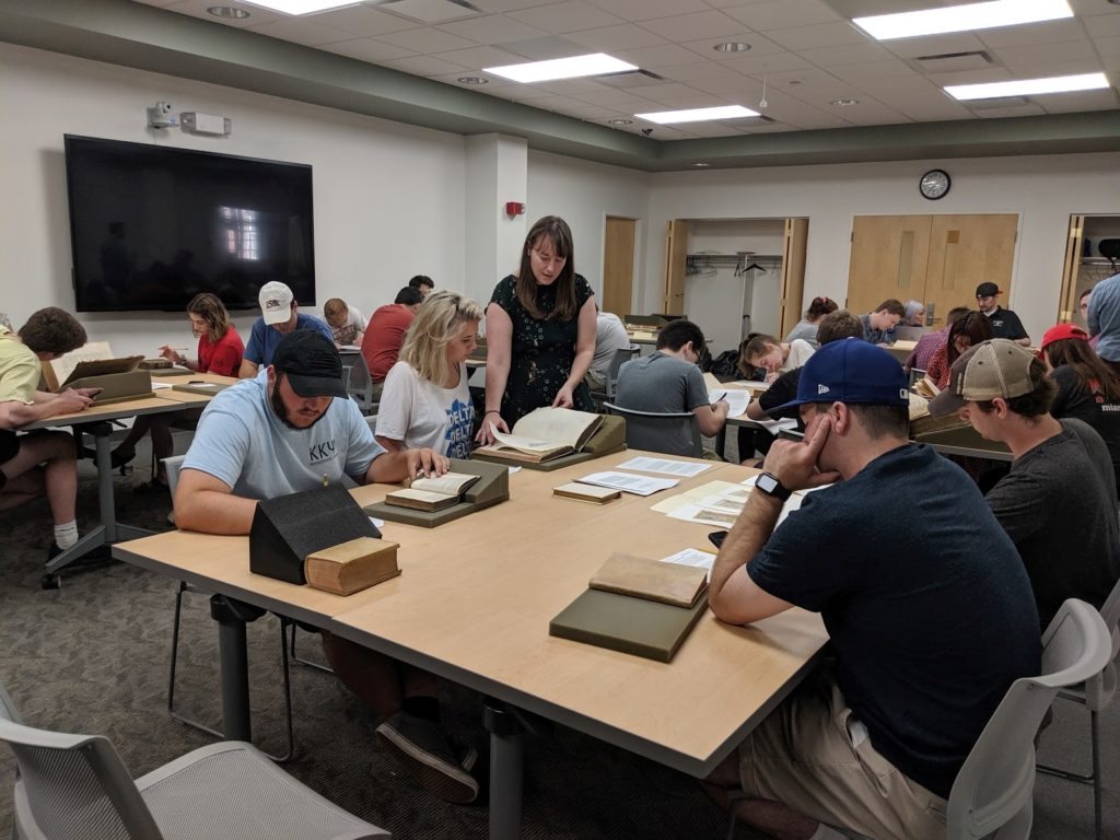 Rachel and students in a classroom looking at special collections materials
