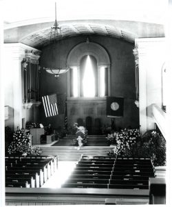 Photograph dated 1945 showing the funeral of a Union College President Dixon Ryan Fox in a church, with coffin in the center and the American flag on the left.