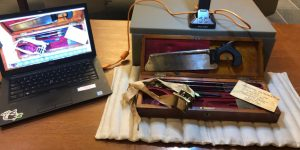 """Image shows a laptop connected to a Hovercam. The hovercam is scanning a wooden box filled with amputation tools. A saw is displayed at the top of the box. A small card reading """"amputation tools"""" is displayed in the bottom right corner of the box."""